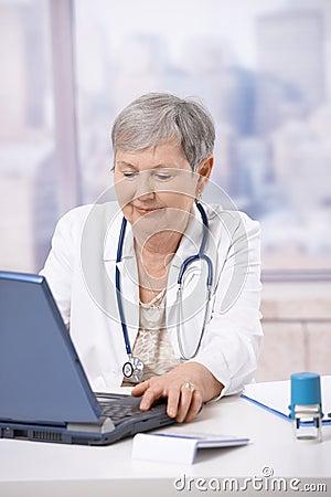 Senior doctor using laptop computer