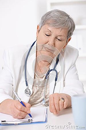Senior doctor writing notes
