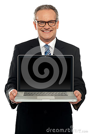 Senior executive standing with open laptop