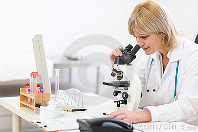 Senior female doctor looking in microscope at lab