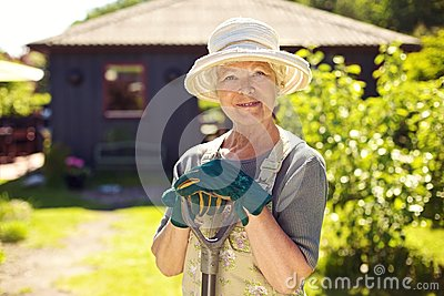 Senior female gardener in backyard with shovel