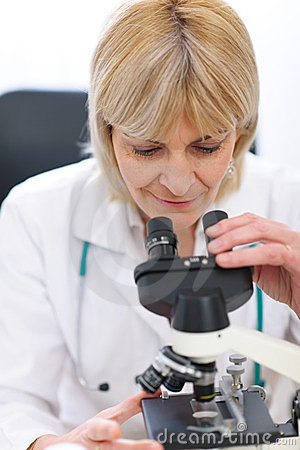 Senior female researcher looking in microscope