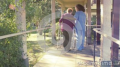 Senior-Frau, die mithilfe ihrer Krankenschwester läuft stock footage