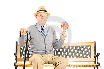 Senior gentleman sitting on a wooden bench and holding a colorfu