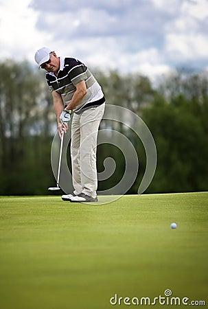 Senior golf player putting.