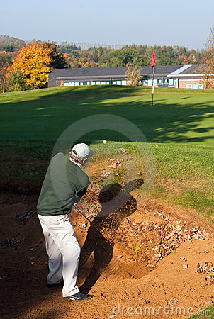 Senior golfer playing out of a bunker in autumn