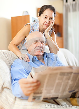 Senior guy with newspaper and mature wife