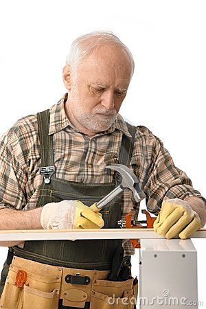 Senior handyman hammering