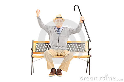 Senior happy man sitting on a bench and gesturing happiness