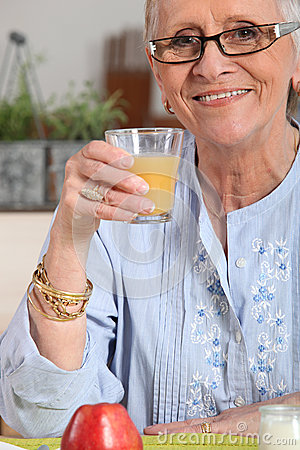 Senior having orange juice
