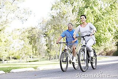 Senior Hispanic Couple Cycling In Park