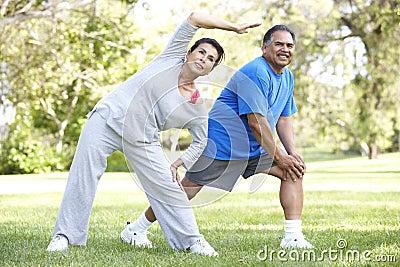 Senior Hispanic Couple Exercising In Park