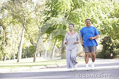 Senior Hispanic Couple Jogging In Park