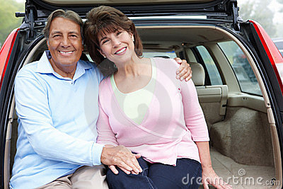 Senior Hispanic couple outdoors with car