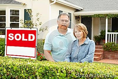 Senior Hispanic couple outside house