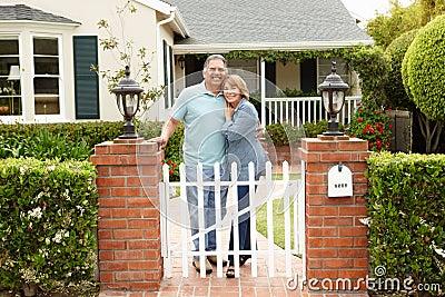 Senior Hispanic couple standing outside home