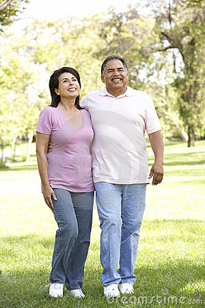 Senior Hispanic Couple Walking In Park