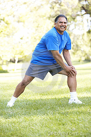Senior Hispanic Man Exercising In Park