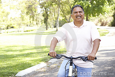 Senior Hispanic Man Riding Bike In Park