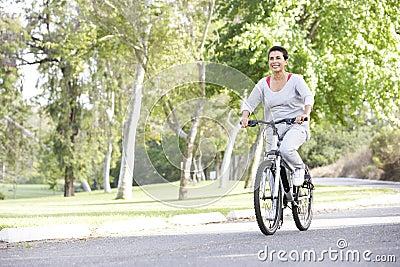 Senior Hispanic Woman Cycling In Park