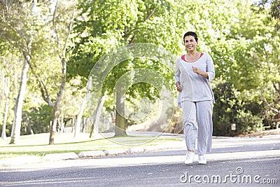 Senior Hispanic Woman Jogging In Park