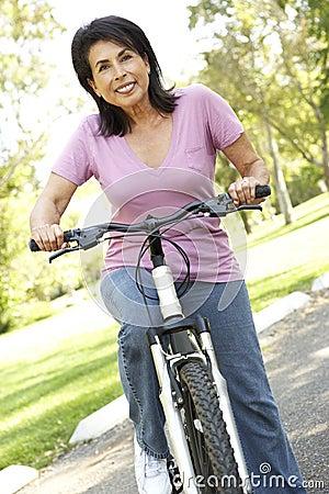 Senior Hispanic Woman Riding Bike In Park