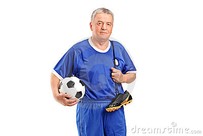 A senior holding a soccer shoes and footbal