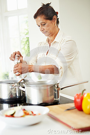 Senior Indian Woman Cooking Meal At Home