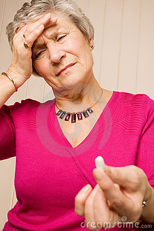 Senior lady with headache holding tablet or pill
