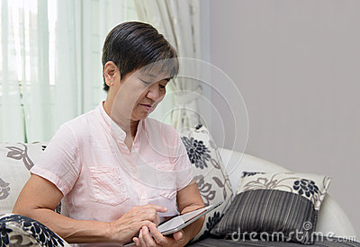 Senior lady playing tablet pc