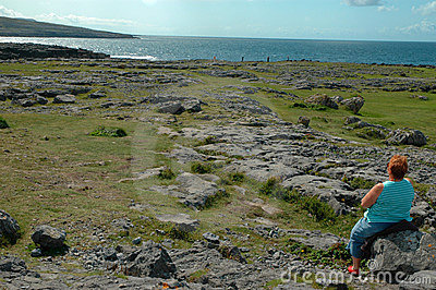 Senior lady sitting on rock looking at sea view