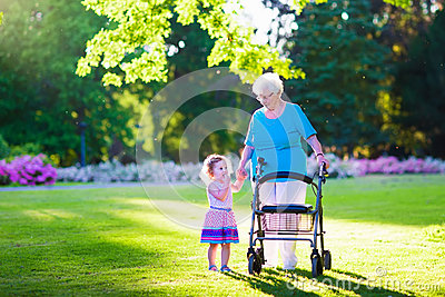 Senior Lady With A Walker And Little Girl In A Park Stock