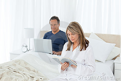 Senior looking at his pc while her wife is reading
