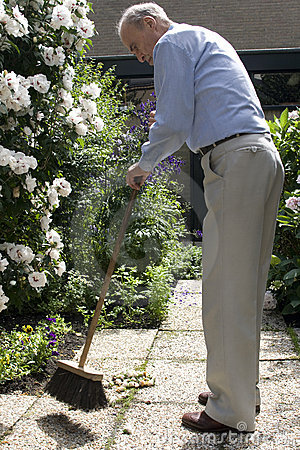Senior male 80+ cleaning garden with broom