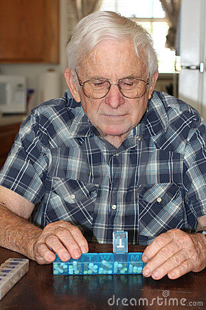 Senior male checks pill box