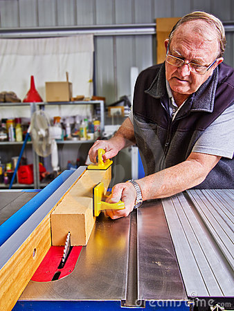 Senior male woodworker using a saw bench