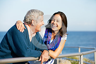 Senior Man With Adult Daughter Looking At Sea