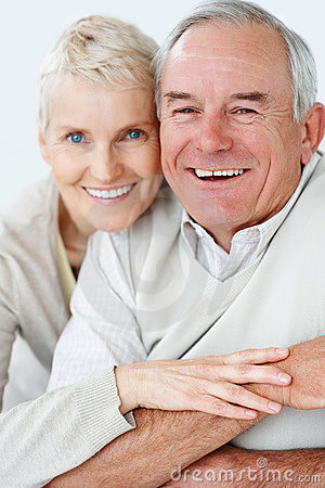 Senior man being hugged by wife from behind