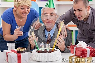 Senior man blowing candles