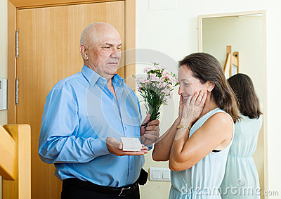 Senior man came to woman with present