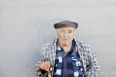 Senior man in checkered jacket at wall