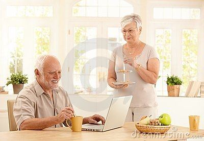 Senior man with computer and coffee in kitchen