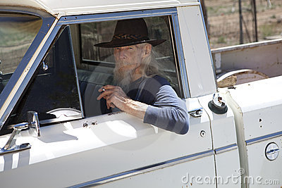 Senior Man With Cowboy Hat Sitting in Vehicle