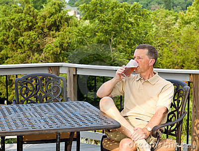 Senior man drinking beer in garden