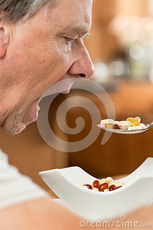 Senior man eating a spoon of vitamins