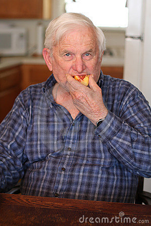 Senior man eats a peach