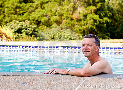 Senior man by edge of swimming pool
