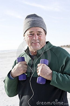 Senior man exercising with hand weights on beach