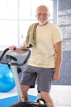 Senior man on fitness cycle smiling