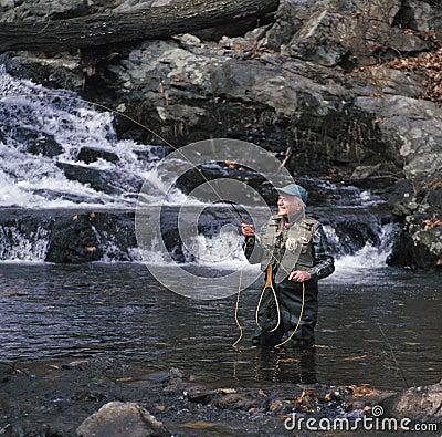 Senior man fly fishing
